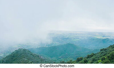 """Stormy weather in mountains. Beautiful view of green hills covered with fog"""