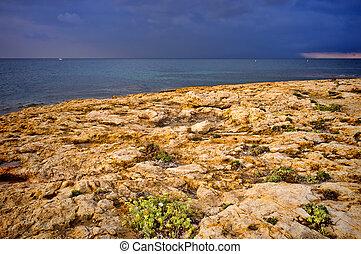 Stormy weather loooming over an idyllic Mediterranean coast