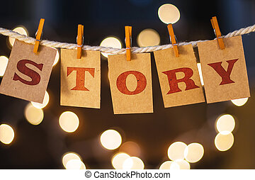 The word STORY printed on clothespin clipped cards in front of defocused glowing lights.