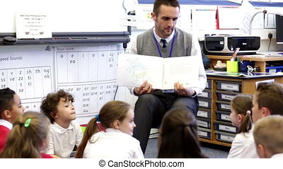 A group of students sit on the floor while a teacher holds a book up and reads to them enthuasiasticly.