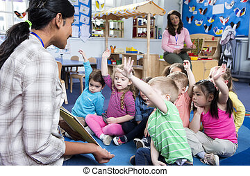Storytime at Nursery - Female teacher giving a lesson to ...