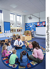 Storytime at Nursery - Group of nursery children sitting on ...