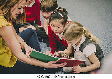 Storytime In The Classroom - Teacher is sitting in the...