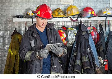 strażak, używając, palcowa pastylka, na, ogień stacja