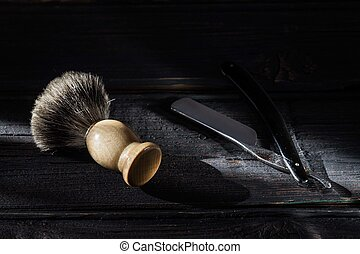 Straight razor and shaving brush on a luxury wooden background