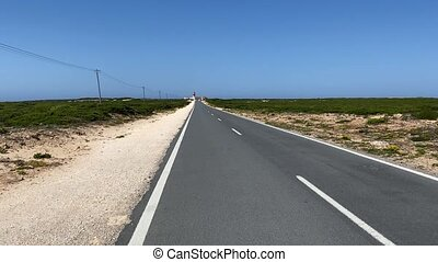 Straight road leading to lighthouse located on the end of Saint Vincent Cape, Algarve, Portugal