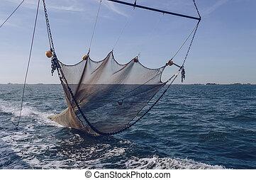 straightened trawler net is going down to sea bottom