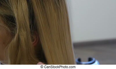 Straightening blond long hair with special ironing in a...