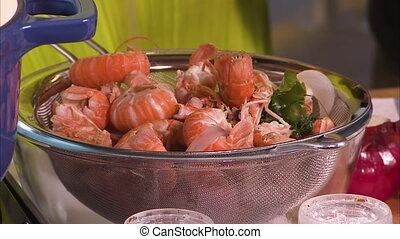 Straining cooked prawns - A steady shot of prawns on a...