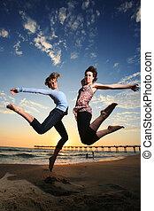 strand, ondergaande zon , springt, meiden, vrolijke