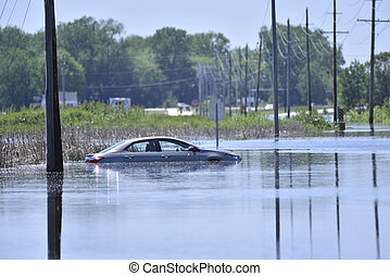 Stranded car on a flooded road - A car sits stranded after...