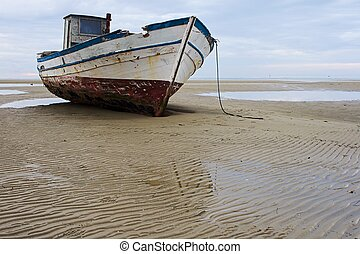 Stranded fishing boat after a storm on the beach at Grado, Italy