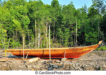 Stranded row boat on dry land in Asian rural area