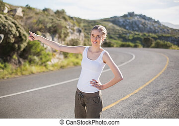 Stranded woman hitching a lift and smiling at camera on a deserted road