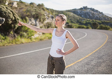 Stranded woman hitching a lift on a deserted country road