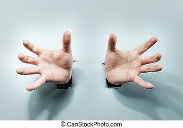 Strange Hands - Strange hands coming through holes in a blue...