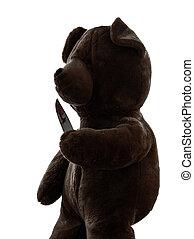 strange killer teddy bear holding bloody knife  silhouette