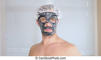 Strange man with face pack. A young man does cosmetic...