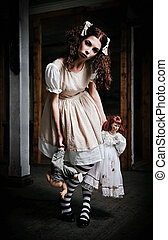 Strange scary girl with dolls in hands