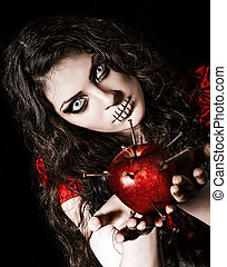 Horror shot: the strange scary girl with mouth sewn shut holds apple studded with nails