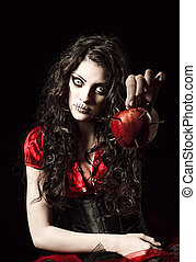 Strange scary girl with mouth sewn shut holds apple studded...
