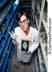 Strange scientist holding fish in formalin