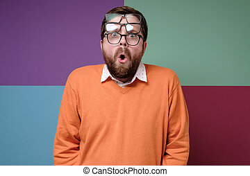 Strange, shocked bearded man put on three pairs of glasses, opened mouth in surprise and with big eyes looks into the camera.