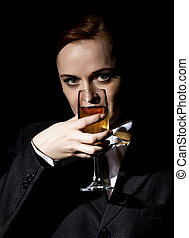 Strange woman in a man's suit drinks champagne on a dark background