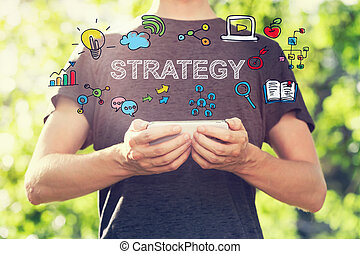 Strategy concept with young man holding his smartphone outside