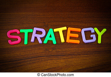 Strategy in colorful toy letters on wood background