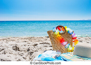 straw bag and hat on the beach