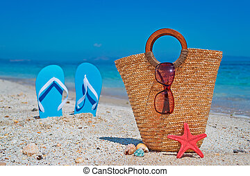 straw bag by the shore with blue sandals on the background