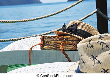 Straw bag and straw hats on plastic lounge chairs on a pier with sea on a background