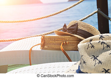 Straw bag and straw hats on plastic lounge chairs on a pier with sea on a background with sunlight