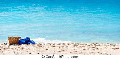 Straw bag and towel at beach