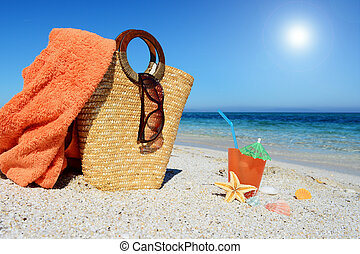 Straw bag, beach towel and cocktail