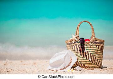 Straw bag, fist star, headphones, hat and sunglasses on white beach