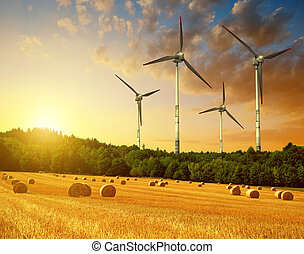 Straw bales with wind turbines on farmland at sunset