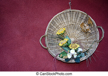 Straw basket with flowers hanging on a red wall