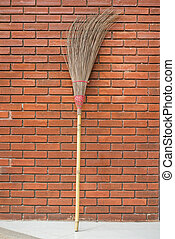 Straw broom against the orage brick wall 1