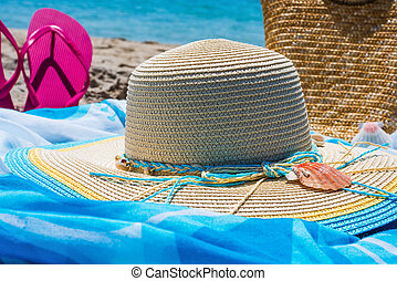 hat and flip flops on the beach
