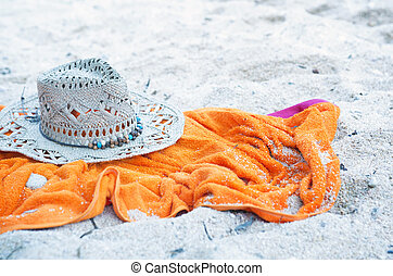 Straw hat and towel on a beach