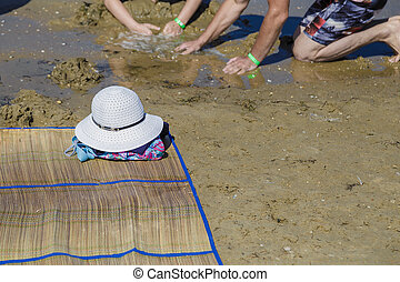 Straw hat, bag, sun glasses and flip flops on a tropical beach.