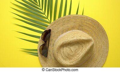 Straw hat, green palm leaf and sunglasses on yellow backdrop. Summer concept. Flat lay, view from top.