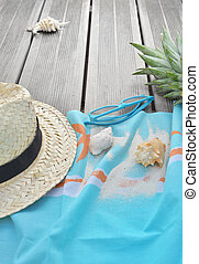 straw hat on beach towel with sunglasses and pineapple on wooden terrace