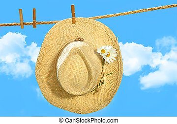 Straw hat on clothesline with blue sky