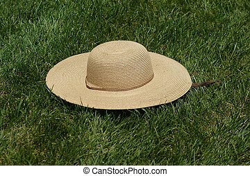 Straw Hat on Grass - A straw hat sitting on grass in summer....