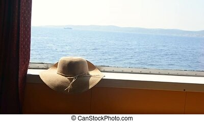 Straw hat on the cabin window on the ferry. Summer travel...