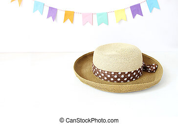 Straw hat on white table with colorful party flags, bunting decoration. Greeting card, invitation for summer birthday or Brazilian june party, Festa Junina holiday. Midsummer celebration.