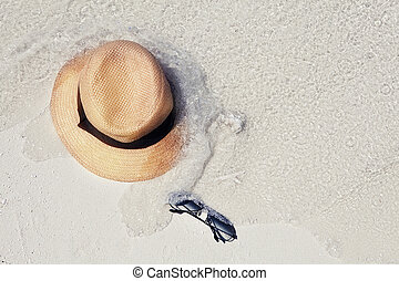 Straw hat, sun glasses on a tropical beach